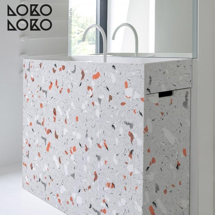 Vinilo para muebles de baño con textura de terrazo en tonos grises y naranjas