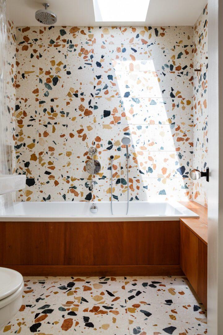 cuarto-de-bano-con-textura-terrazo-naranjas-y-verdes